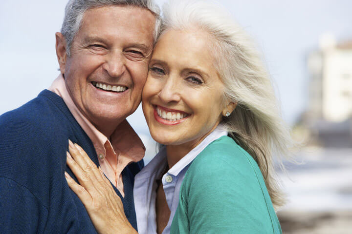 Romantic Senior Couple Hugging On Beach