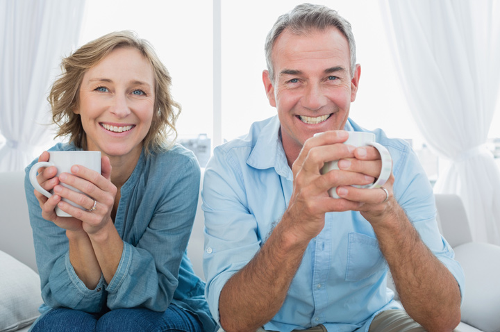Over 55 Singles Smiling middle aged couple sitting on the couch